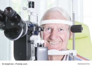Portrait älterer Patient bei der Spaltlampenuntersuchung in einer Augenarztpraxis